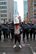 Photo: A man wearing a red bandana on his face holds up a sign in front of a line of riot police in downtown Toronto.