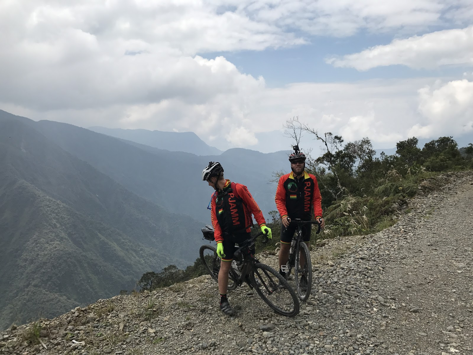 Cyclist with bike looking over cliff on Death Road