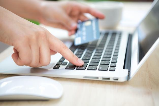 Mão com um cartão de crédito e um computador portátil