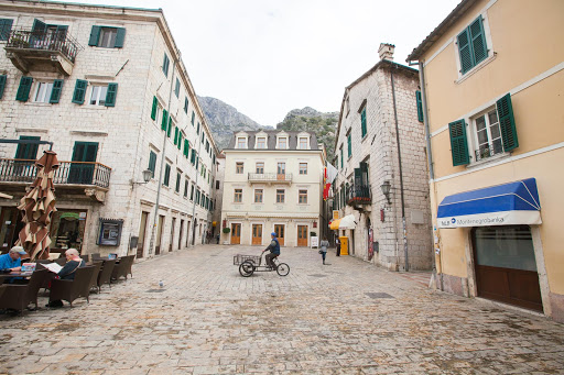 A square in Kotor's Stari Grad, or Old Town, lined with elegant stone houses and thin lanes.