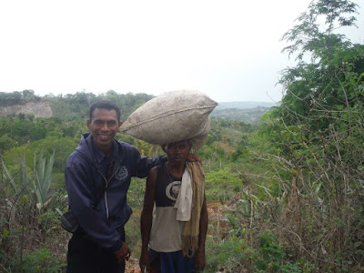 Nimrod photo bombing a picture of a man carrying a bag on his head in timor west | Krys Kolumbus Travel Blog