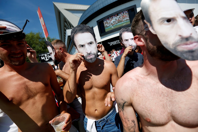 Soccer fans in Bristol don masks of England manager Gareth Southgate as they celebrate their nation's World Cup victory over Sweden.