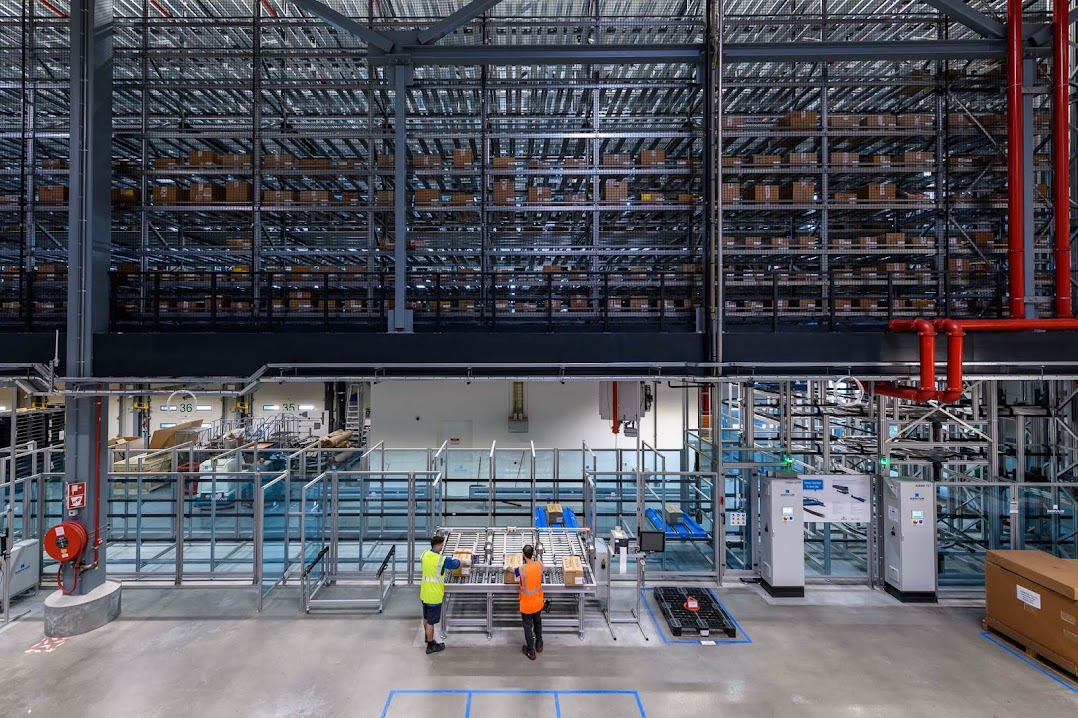 サプライヤーの工場内で、商品をベルトコンベアに載せる 2 人の作業員。