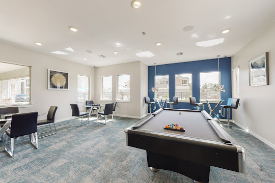 Community clubhouse billiards room with lounge seating and pool table