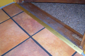 """Photo: The floor is officially done! Here's a picture of the transition piece between the tiles and the door's threshold. I was unable to find a good transition that would work for my floor, so I ended up using a brass carpet bar and 3"""" screws to cover the gap. In the picture, you can also see the gray caulk I used to seal the expansion gaps around the room's perimeter, and the grout lines have been sealed! So....I'm really, truly done with the floor! :)"""