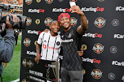 Anga Makubalo, better known as NaakMusiq and Orlando Pirates midfielder Thembinkosi Lorch during the Carling Black Label Cup match between Orlando Pirates and Kaizer Chiefs at FNB Stadium on July 27, 2019 in Johannesburg, South Africa.