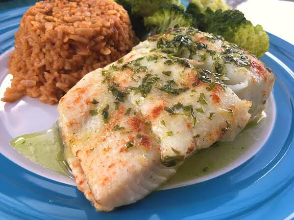 A Halibut Fillet With Butter Sauce On Top Sitting On A Blue Plate With Rice And Broccoli.