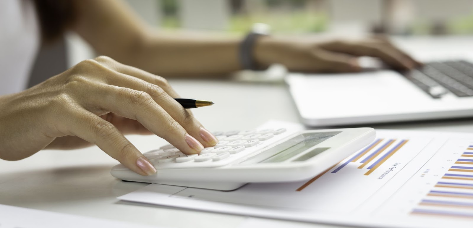 Woman working using a laptop and a calculator