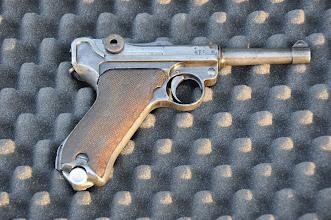 """Photo: Německá samonabíjecí pistole Luger P.08 – hojně užívaná za 1. a 2. světové války.  Známá spíše pod názvem """"Parabella"""". Později nahrazena pistolí P38, typická zbraň Gestapa. Američané často obírali mrtvá těla německých důstojníků, protože pistole P.08 pro ně byla jakási trofej. Spousta těchto zbraní je dodnes rozkradená v USA. U pistole je typický kloubový mechanizmus závěru (obrázek 14.).  Autor popisku: Štěpán Pravda, student 1. A."""