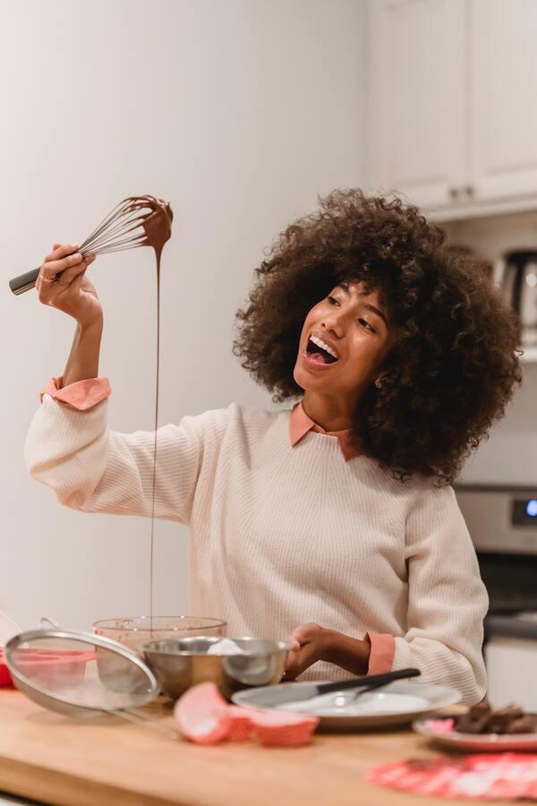 Mulher negra cozinhando uma massa de chocolate