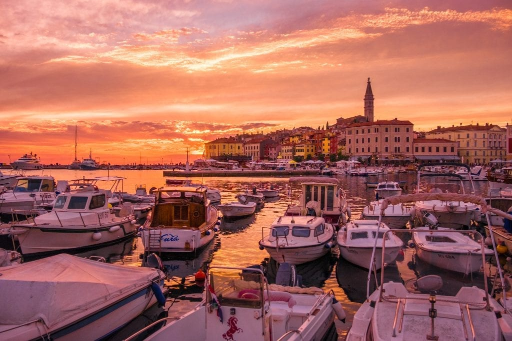 A stunning orange-yellow-pink sunset with the tower of Rovinj in the background; in the foreground are small white boats.