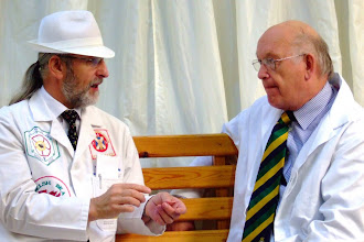 Photo: Michael Badger MBE and Master Honey judge discussing finer points with Michael Young.