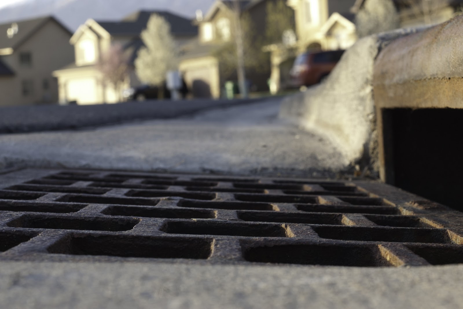 a storm drain with a drainage grate on a curb in a suburban neighborhood