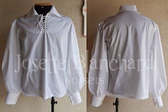 Photo: Camisa Medieval em algodão branco com mangas largas, ilhóses no decote e punhos. A partir de R$ 100,00.