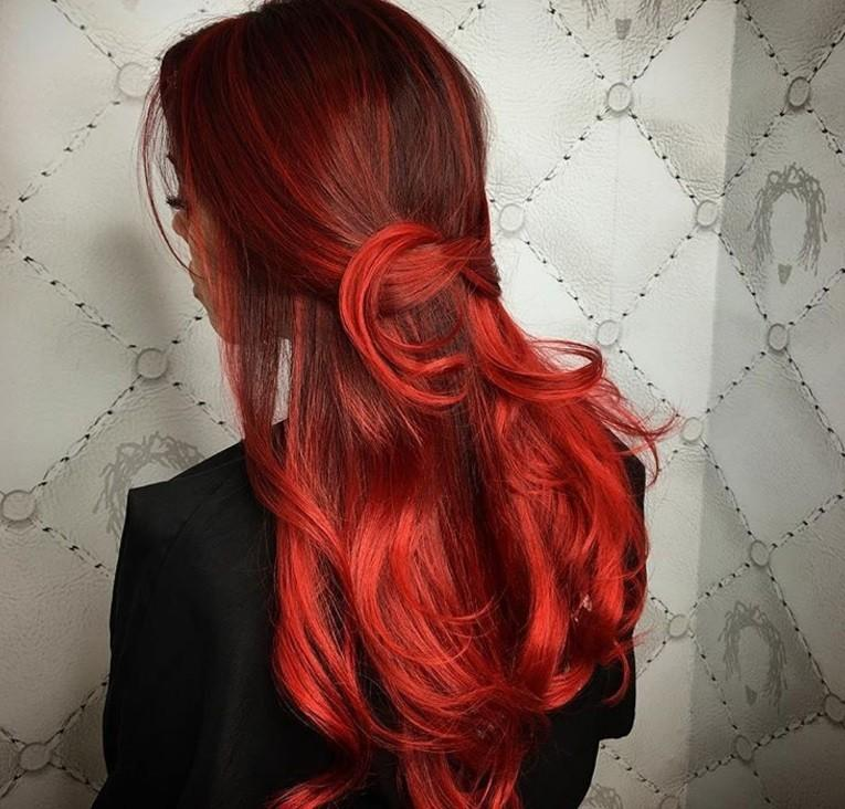 Red highlight: Back shot of a woman with dark black to red hair tied in a loose half-up half-down hairstyle