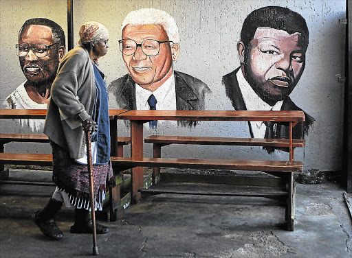ESTEEMED COMPANY: Sarah Kunene, 84, walks past a mural depicting ANC leaders Oliver Tambo, Walter Sisulu and former president Nelson Mandela at a spaza shop in Soweto yesterday. Mandela is undergoing medical tests