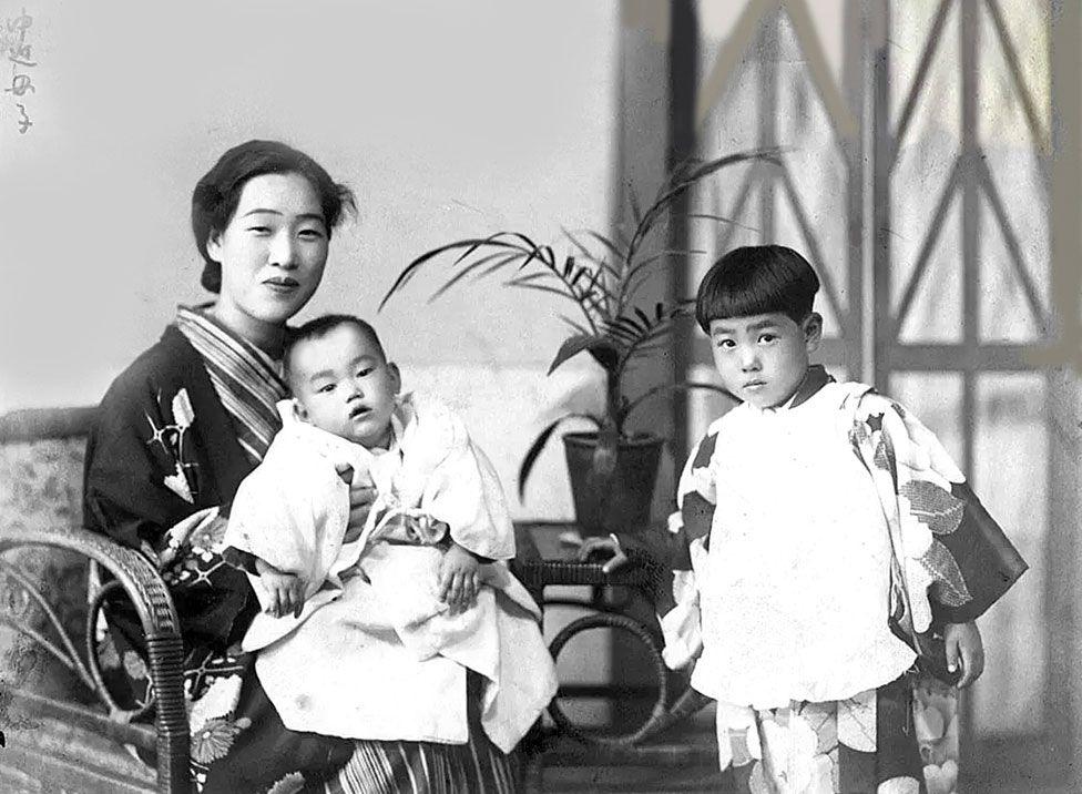 Еміко на руках матері Фуку Накасако та її сестра Мієко