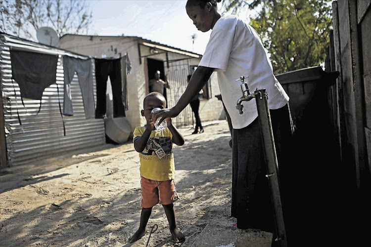 Thembi Mogoba gives her son, Kgothatso, water from a tap outside their home. File photo.