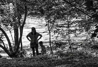Photo: Silhouettes of a mother and child on the banks of the Red Cedar River