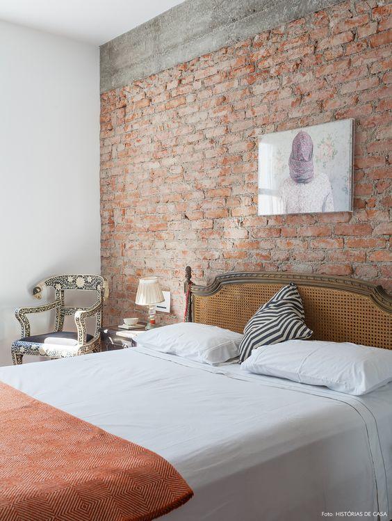 Quarto em estilo rústico com cama de casal com cabeceira antiga pequena e parede de tijolinhos.