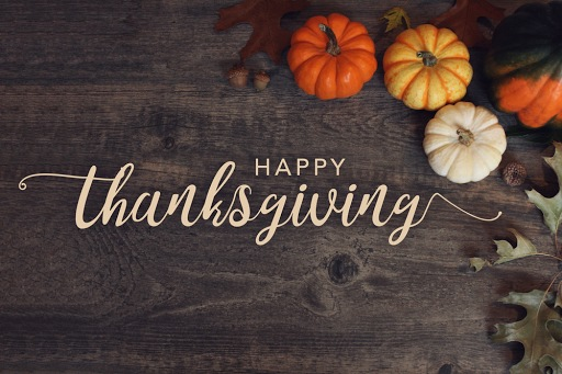 Pumpkins, acorns, and leaves on a wooden background with the text Happy Thanksgiving overall