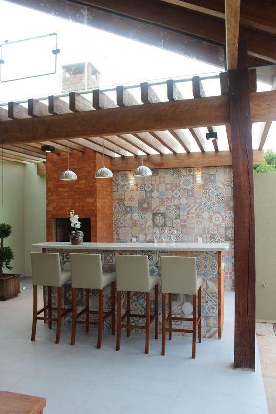 Area externa com churrasqueira de tijolinhos, bancada de porcelanato branco, bancos com estrutura de madeira e estofado cinza e papel de parede imitando ladrilhos hidraulicos.