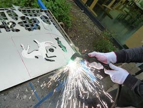 Photo: Beim Wasserspiel Künstler-Schul-Projekt gehts richtig zur Sache, die Kinder bohren und montieren Dosen, entwerfen um dann mit dem Plasmaschneider ihre Gestaltung selbst auszuschneiden und dann farblich auf den Wasserrädern zu bemalen,