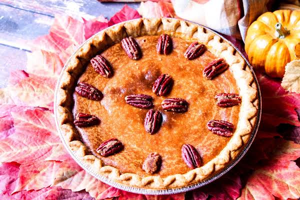 Creamy Pumpkin Pie With Candied Pecans Ready To Be Served.