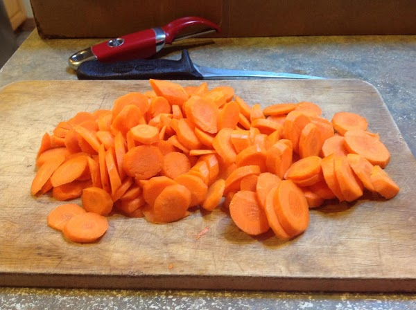 While chicken parts are cooking, peel and slice carrots.