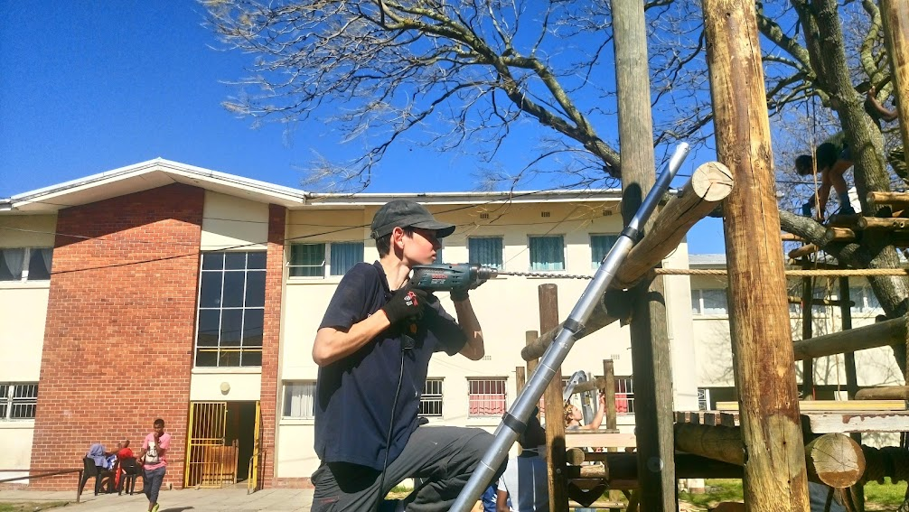 Charles drilling holes to bolt the poles onto the side of the house