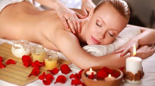 a lady receiving a massage with candles and petals next to her