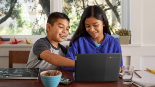 young boy and girl looking at computer at the same time