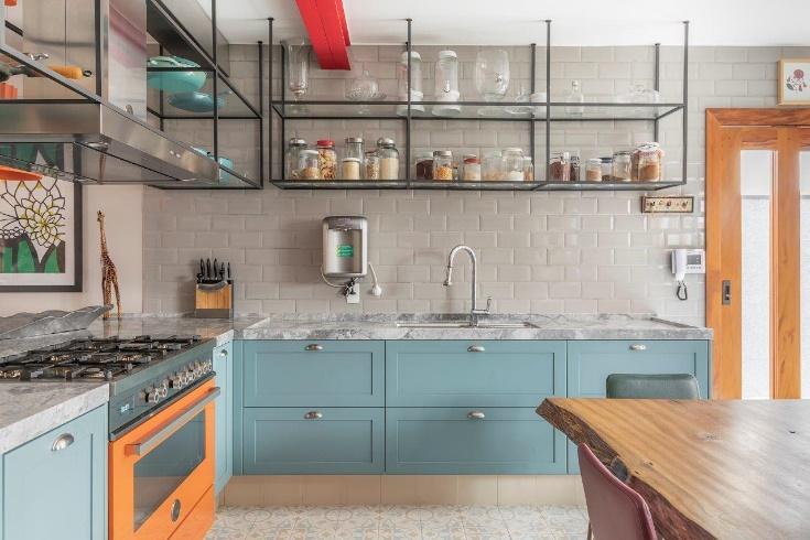 Cozinha industrial com azulejo do metrô branco, com bancada de porcelanato que reproduz pedras, armário de ferro suspenso no teto e armários na cor azul claro.