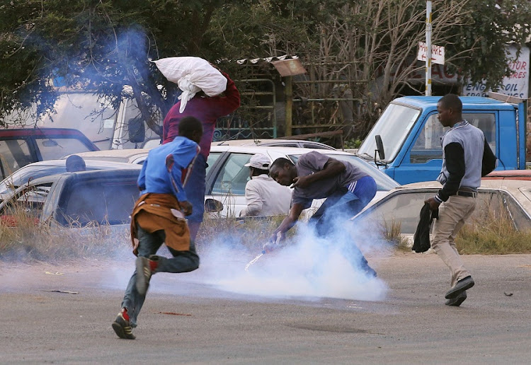 Residents of Epworth suburb flee as riot police fire teargas after a protest by taxi drivers turned violent in Harare last year. Picture: REUTERS