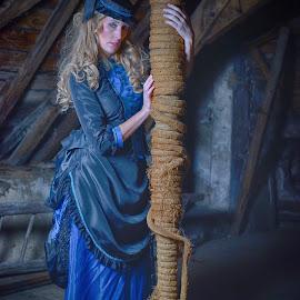 Blue Manu by Marco Bertamé - People Portraits of Women ( woman, rope, blon, copped, pole, brown, portrait, cord, bar, blue, robe, lady, hat )