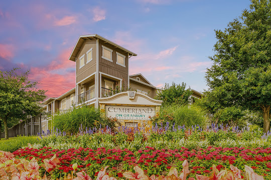 Apartment community welcome sign with flowers and landscaping surrounding