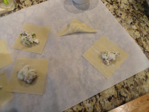 Fill wonton wrappers with about 1 teaspoon cream cheese mixture each. Moisten edges with...