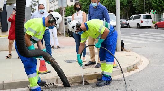 Dos operarios realizando las tareas de limpieza de un imbornal
