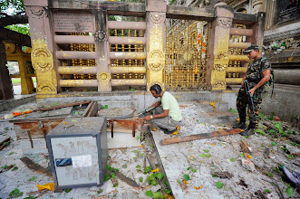 """Photo: Indian security personnel inspect the site of an explosion inside the Mahabodhi temple complex at Bodh Gaya in the eastern Indian state of Bihar July 7, 2013. A series of explosions in and around Buddhism's holiest shrine in Bihar injured two persons early on Sunday, in what the government described as a """"terror"""" attack. The Mahabodhi Temple complex is located in Bodh Gaya, the place where the Buddha is believed to have attained enlightenment.    REUTERS/Krishna Murari Kishan (INDIA - Tags: POLITICS DISASTER RELIGION) - RTX11FHD"""