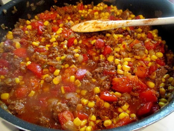 Add the seasonings, tomatoes, broth, corn, olives and simmer for 10 minutes.