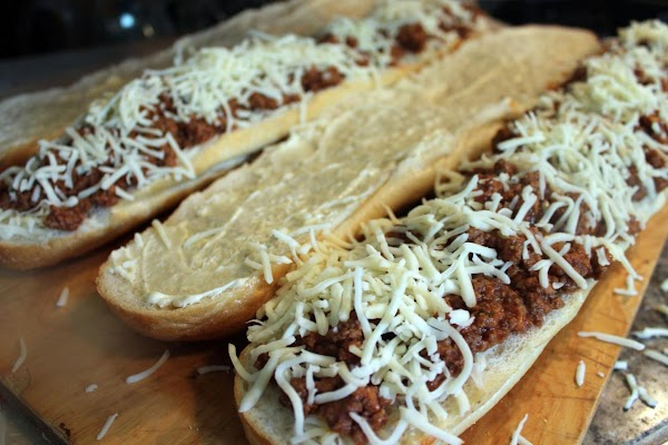 Cheese sprinkled on top of meat mixture on garlic bread.