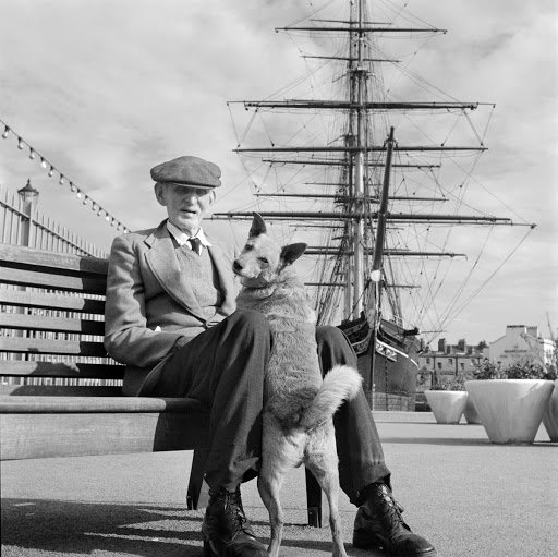 An elderly man and his dog seated in front of 'Cutty Sark', Greenwich, London