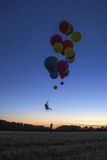 Tom Morgan flew 25km in a camping chair attached to a host of helium balloons.