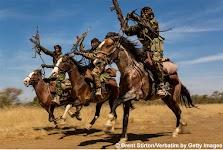 3 mannen in militaire uitrusting in galop te paard