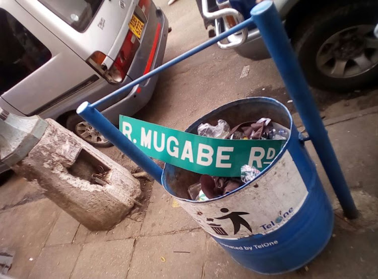 Road sign for R. Mugabe road ripped off and dumped by people marching in Harare.
