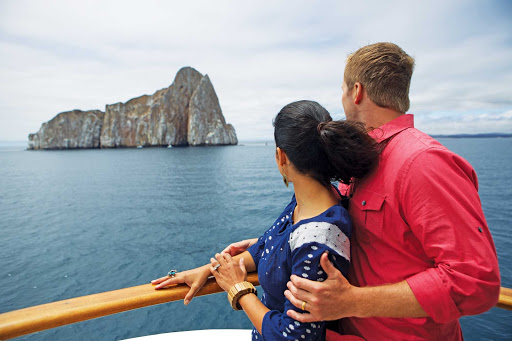 Celebrity-Xpedition-couple-Kicker-Rock - A couple on Celebrity Xpedition watches Kicker Rock (or León Dormido), a spectacular volcanic rock formation in the Galapagos that towers 460 feet above the sea.
