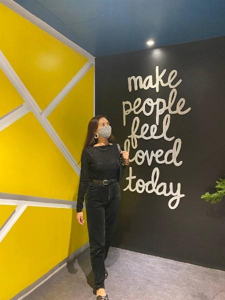 A person standing in front of a wall with writing on itDescription automatically generated with medium confidence