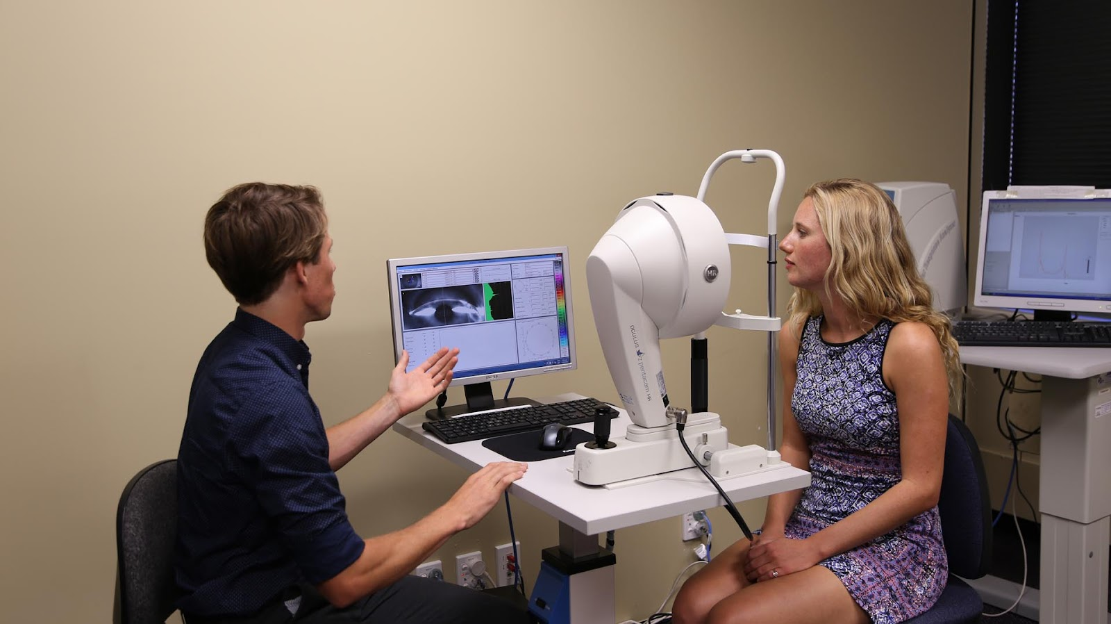 An individual talking to a patient about the results of the corneal topography scan.