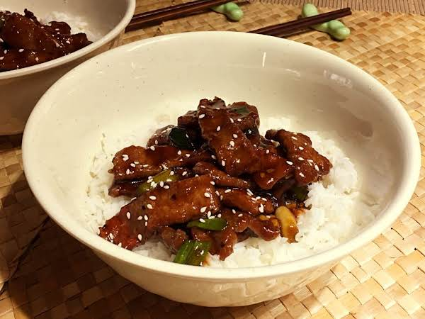 Beef Strips In A Dark Sauce Sitting On A Bed Of White Rice.