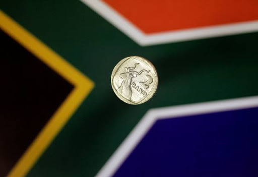 FILE PHOTO: Illustration photo shows a two-rand coin above a South Africa flag.